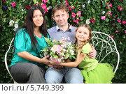 Купить «Молодая семья с двумя детьми сидит на плетеной скамейке около живой изгороди», фото № 5749399, снято 13 января 2013 г. (c) Losevsky Pavel / Фотобанк Лори