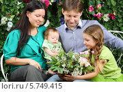 Купить «Счастливая семья с цветами в саду», фото № 5749415, снято 13 января 2013 г. (c) Losevsky Pavel / Фотобанк Лори