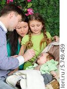 Купить «Счастливая семья кормит малыша в люльке», фото № 5749459, снято 13 января 2013 г. (c) Losevsky Pavel / Фотобанк Лори
