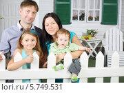 Купить «Мама, папа, сын и дочь около забора около коттеджа», фото № 5749531, снято 13 января 2013 г. (c) Losevsky Pavel / Фотобанк Лори