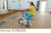 Купить «Полная женщина занимается на велотренажере», видеоролик № 5750615, снято 27 марта 2014 г. (c) Михаил Коханчиков / Фотобанк Лори