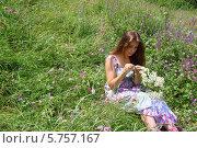 Молодая девушка в платье сидит на зеленом лугу с букетом из ромашек. Стоковое фото, фотограф Бережная Татьяна / Фотобанк Лори