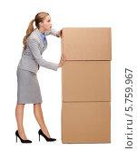 Купить «Молодая женщина в строгом деловом костюме пытается сдвинуть картонные коробки», фото № 5759967, снято 19 января 2014 г. (c) Syda Productions / Фотобанк Лори