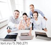"""Купить «Успешные молодые деловые люди в офисе показывают жест """"отлично"""", сидя за столом с ноутбуками», фото № 5760271, снято 9 июня 2013 г. (c) Syda Productions / Фотобанк Лори"""
