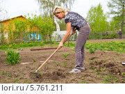 Купить «Женщина разравнивает землю граблями в весеннем саду», фото № 5761211, снято 25 мая 2013 г. (c) Евгений Ткачёв / Фотобанк Лори
