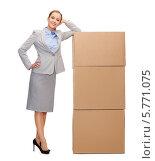 Купить «Привлекательная бизнес-леди в сером деловом костюме стоит, облокотившись на картонные коробки», фото № 5771075, снято 19 января 2014 г. (c) Syda Productions / Фотобанк Лори