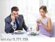 Купить «Молодой человек в деловом костюме разговаривает по сотовому телефону, сидя за столиком в ресторане со свое девушкой», фото № 5771159, снято 9 марта 2014 г. (c) Syda Productions / Фотобанк Лори