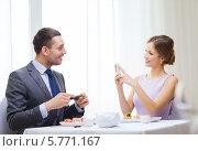 Купить «Улыбающаяся девушка фотографирует на смартфон своего друга в ресторане», фото № 5771167, снято 9 марта 2014 г. (c) Syda Productions / Фотобанк Лори