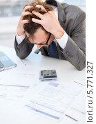 Купить «Стресс на работе. Служащий обхватил голову руками и смотрит на документы, разложенные на столе», фото № 5771327, снято 3 октября 2013 г. (c) Syda Productions / Фотобанк Лори