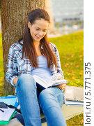 Купить «Девушка читает кгнигу, сидя под деревом в парке», фото № 5771375, снято 15 сентября 2013 г. (c) Syda Productions / Фотобанк Лори