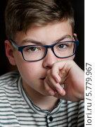 Купить «Портрет задумчивого юного парня в очках от зрения», эксклюзивное фото № 5779967, снято 1 апреля 2014 г. (c) Игорь Низов / Фотобанк Лори