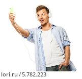 Красивый молодой человек в наушниках фотографирует себя на телефон на белом фоне. Стоковое фото, фотограф Andrejs Pidjass / Фотобанк Лори
