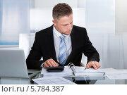 Купить «бизнесмен анализирует отчеты», фото № 5784387, снято 25 января 2014 г. (c) Андрей Попов / Фотобанк Лори
