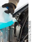 Купить «Водитель заливает специальную жидкость в бачок омывателя автомобиля», фото № 5786555, снято 16 января 2014 г. (c) Syda Productions / Фотобанк Лори