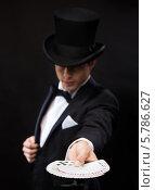 Купить «Фокусник во фраке и в цилиндре показывает фокус с картами», фото № 5786627, снято 12 сентября 2013 г. (c) Syda Productions / Фотобанк Лори