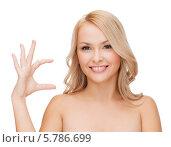 Купить «Девушка держит в руке невидимый предмет», фото № 5786699, снято 7 января 2014 г. (c) Syda Productions / Фотобанк Лори