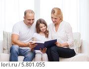 Купить «Маленькая девочка с родителями читают сидят на диване и читают книгу», фото № 5801055, снято 1 марта 2014 г. (c) Syda Productions / Фотобанк Лори