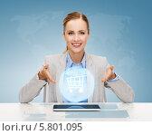 Купить «Улыбающаяся бизнесвумен сидит за столом и показывает на планшетный компьютер и виртуальный значок тележки для покупок», фото № 5801095, снято 19 января 2014 г. (c) Syda Productions / Фотобанк Лори