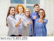 Купить «Дружный коллектив. Коллеги в офисе все вместе вытянули вперед руки с поднятым вверх большим пальцем», фото № 5801255, снято 1 февраля 2014 г. (c) Syda Productions / Фотобанк Лори
