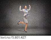 Купить «Молодая женщина в деловом костюме радостно прыгает на фоне серой стены», фото № 5801427, снято 21 января 2018 г. (c) Syda Productions / Фотобанк Лори