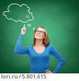 Купить «Девушка в очках улыбается и думает о чем-то, подняв вверх указательный палец», фото № 5801615, снято 5 декабря 2013 г. (c) Syda Productions / Фотобанк Лори