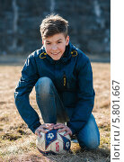 Купить «Весёлый юный парень сидит с футбольным мячом на футбольном поле», эксклюзивное фото № 5801667, снято 11 апреля 2014 г. (c) Игорь Низов / Фотобанк Лори