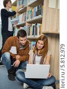 Купить «Одногруппники вместе занимаются сидя на полу в библиотеке с ноутбуком», фото № 5812979, снято 23 марта 2014 г. (c) CandyBox Images / Фотобанк Лори