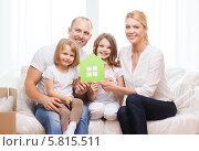 Купить «Дружная семья с двумя детьми держат в руках зеленый домик, вырезанный из картона», фото № 5815511, снято 1 марта 2014 г. (c) Syda Productions / Фотобанк Лори