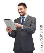 Позитивный молодой бизнесмен в строгом костюме читает новости на экране планшетного компьютера, фото № 5815919, снято 15 марта 2014 г. (c) Syda Productions / Фотобанк Лори