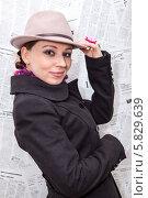 Купить «Молодая женщина в шляпе и пальто напротив фона из газет», фото № 5829639, снято 10 апреля 2014 г. (c) Кекяляйнен Андрей / Фотобанк Лори