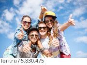 Счастливые друзья в солнцезащитных очках радуются солнечному дню на фоне голубого неба. Стоковое фото, фотограф Syda Productions / Фотобанк Лори