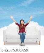 Купить «Девушка сидит на диване и слушает музыку в наушниках. Руки подняты вверх», фото № 5830659, снято 26 февраля 2014 г. (c) Syda Productions / Фотобанк Лори