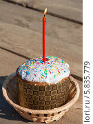 Купить «Пасхальный кулич с красной свечёй стоит на деревянном столе», эксклюзивное фото № 5835779, снято 19 апреля 2014 г. (c) Lora / Фотобанк Лори