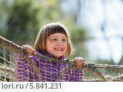Маленькая девочка смеется и держится за канаты. Стоковое фото, фотограф Яков Филимонов / Фотобанк Лори