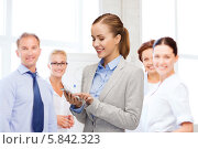 Купить «Молодая бизнес-леди в строгом деловом костюме набирает номер на смартфоне, стоя на фоне своих коллег», фото № 5842323, снято 19 января 2014 г. (c) Syda Productions / Фотобанк Лори