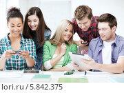 Купить «Друзья общаются в аудитории, читая сообщения на смартфоне и планшетном компьютере», фото № 5842375, снято 16 июня 2013 г. (c) Syda Productions / Фотобанк Лори