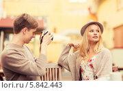 Купить «Молодой человек фотографирует девушку, смотрящую в сторону, за столиком уличного кафе», фото № 5842443, снято 6 сентября 2013 г. (c) Syda Productions / Фотобанк Лори