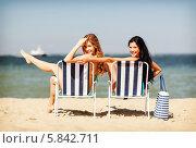 Купить «Симпатичные подруги сидят в шезлонгах на пляже у моря», фото № 5842711, снято 11 июля 2013 г. (c) Syda Productions / Фотобанк Лори