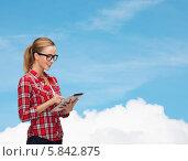 Купить «Скромная студентка в очках смотрит на экран планшетного компьютера», фото № 5842875, снято 19 января 2014 г. (c) Syda Productions / Фотобанк Лори