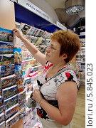 Купить «Женщина выбирает сувенирные открытки в магазине, Мюнхен», эксклюзивное фото № 5845023, снято 30 июля 2013 г. (c) Илюхина Наталья / Фотобанк Лори