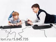 Отец и сын играют вместе в компьютерную игру, лежа на полу. Стоковое фото, фотограф Daniil Nikiforov / Фотобанк Лори