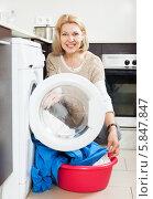 Купить «Домохозяйка с тазом грязного белья сидит возле стиральной машины», фото № 5847847, снято 19 марта 2014 г. (c) Яков Филимонов / Фотобанк Лори