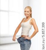 Купить «Девушка-блондинка в больших джинсах стоит у окна в комнате и улыбается, радуясь снижению веса», фото № 5857399, снято 23 марта 2013 г. (c) Syda Productions / Фотобанк Лори