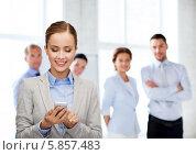Купить «Молодая деловая женщина улыбается, читая смс-сообщение в офисе», фото № 5857483, снято 19 января 2014 г. (c) Syda Productions / Фотобанк Лори