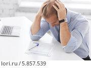 Купить «Стресс на работе. Бизнесмен сидит за столом в офисе, обхватив голову руками», фото № 5857539, снято 9 июня 2013 г. (c) Syda Productions / Фотобанк Лори