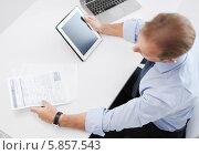 Бизнесмен в офисе сидит за рабочим столом с планшетным компьютером и документами. Стоковое фото, фотограф Syda Productions / Фотобанк Лори