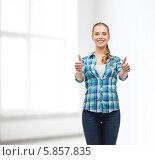 """Купить «Молодая женщина в повседневной одежде показывает обеими руками жест """"отлично"""", стоя у окна в своей квартире», фото № 5857835, снято 12 февраля 2014 г. (c) Syda Productions / Фотобанк Лори"""