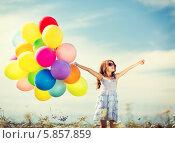 Счастливая девочка со связкой разноцветных воздушных шаров стоит на улице, раскинув руки в стороны. Стоковое фото, фотограф Syda Productions / Фотобанк Лори
