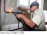 Сварщик варит трубу при замене батарей (2013 год). Редакционное фото, фотограф Андрей Гривцов / Фотобанк Лори