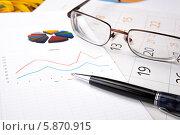 Купить «Бумаги с графиками, очки и шариковая ручка на рабочем столе», фото № 5870915, снято 1 мая 2014 г. (c) Александр Калугин / Фотобанк Лори